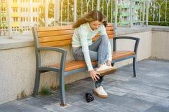 El adolescente que se sienta en un banco en la ciudad viste las ruedas en las zapatillas de deporte Imagen de archivo libre de regalías
