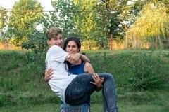 El adolescente que sonríe, muchacho en el ` feliz s de la muchacha arma Fotos de archivo