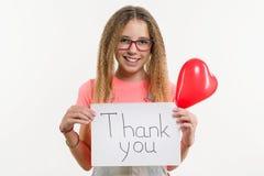 El adolescente que sostiene un papel con el texto le agradece, globo del corazón, fondo blanco del estudio Fotografía de archivo libre de regalías