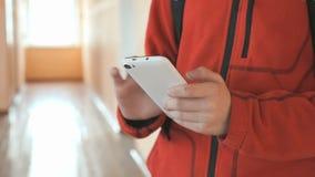 El adolescente que sostiene un teléfono móvil blanco dentro almacen de metraje de vídeo
