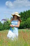 El adolescente recoge las flores del verano Fotos de archivo