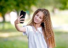El adolescente rizado lindo de la muchacha hace el selfie Imagenes de archivo