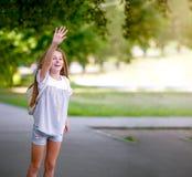 El adolescente rizado lindo de la muchacha saluda alguien Foto de archivo