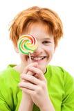 El adolescente rojo con un caramelo de azúcar Imagenes de archivo