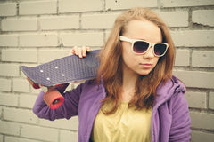 El adolescente rubio agradable en gafas de sol sostiene el monopatín Foto de archivo