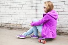 El adolescente rubio en gafas de sol se sienta en el monopatín Imagenes de archivo