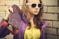 El adolescente rubio en gafas de sol sostiene el monopatín Imágenes de archivo libres de regalías