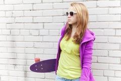 El adolescente rubio en gafas de sol sostiene el monopatín Foto de archivo