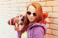 El adolescente rubio en gafas de sol sostiene el monopatín Imagen de archivo