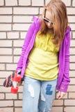 El adolescente rubio en gafas de sol sostiene el monopatín Imagenes de archivo