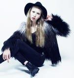 El adolescente rubio joven en el sombrero y el abrigo de pieles, moda vistió el modelo, tiro del estudio Fotos de archivo