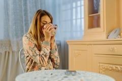 El adolescente rubio joven está bebiendo té mientras que se sienta en la silla Imagen de archivo