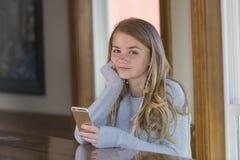 El adolescente rubio joven goza el escuchar la música Imagen de archivo libre de regalías