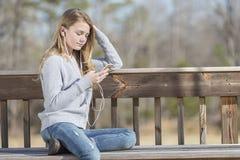 El adolescente rubio joven goza el escuchar la música Fotografía de archivo