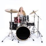 El adolescente rubio joven juega los tambores en estudio contra blanco Fotografía de archivo
