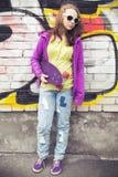 El adolescente rubio sostiene el monopatín, foto vertical Imagen de archivo