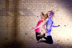 El adolescente salta contra fondo de la pared de ladrillo Fotos de archivo