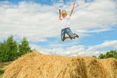 El adolescente salta en el heno Muchacho feliz Fotografía de archivo