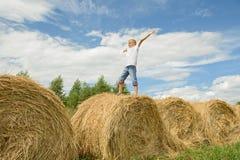 El adolescente salta en el heno Muchacho feliz Imagen de archivo