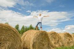 El adolescente salta en el heno Muchacho feliz Fotos de archivo libres de regalías