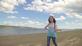 El adolescente salta a lo largo de la playa y escucha la música almacen de video