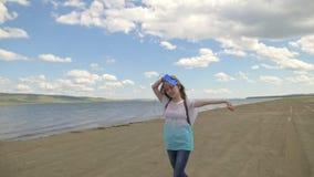 El adolescente salta a lo largo de la playa y escucha la música