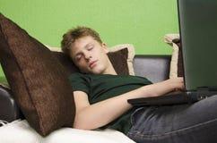 El adolescente se cayó dormido con un ordenador portátil Fotografía de archivo libre de regalías