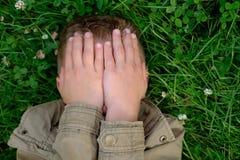 El adolescente se cierra los ojos con las manos Fotos de archivo