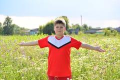 El adolescente se coloca en los brazos del prado extendidos a los lados Imagen de archivo libre de regalías