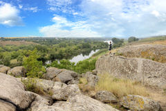 El adolescente se coloca encima de un canto rodado de piedra grande en el banco del río meridional del insecto y mira el río abaj Foto de archivo