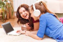 El adolescente se divierte con su madre que usa el ordenador portátil Fotografía de archivo