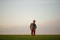 El adolescente se está colocando en la hierba alta en la puesta del sol Fotografía de archivo