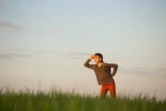 El adolescente se está colocando en la hierba alta en la puesta del sol Imagenes de archivo