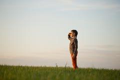 El adolescente se está colocando en la hierba alta en la puesta del sol Imágenes de archivo libres de regalías