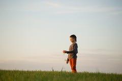 El adolescente se está colocando en la hierba alta en la puesta del sol Fotos de archivo