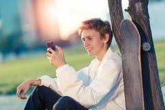 El adolescente se está sentando con un teléfono en su mano Fotos de archivo libres de regalías