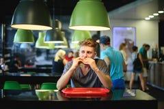 El adolescente se está sentando en un restaurante de comida rápida, comiendo una hamburguesa grande, hermosa y mirando lejos Imágenes de archivo libres de regalías