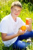 El adolescente se está sosteniendo de cristal con el zumo de naranja Imágenes de archivo libres de regalías