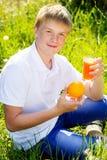 El adolescente se está sosteniendo de cristal con el zumo de naranja Fotografía de archivo libre de regalías