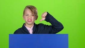 El adolescente se levanta de detrás las miradas del tablero en él y la aversión de las demostraciones en una pantalla verde Cámar metrajes
