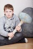 El adolescente se sienta con la cara cruel con el hacha de piedra Fotografía de archivo