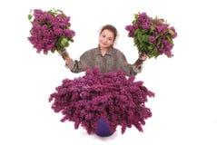 El adolescente se sienta con la lila en ambas manos Imagen de archivo