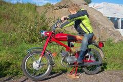 El adolescente se sienta en el viejo ` del ` Verkhovyna-6 del ciclomotor del oviet del ‹de Ñ Exposición del transporte retro en K Fotografía de archivo libre de regalías