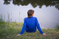 El adolescente se sienta en la orilla del lago Fotografía de archivo libre de regalías