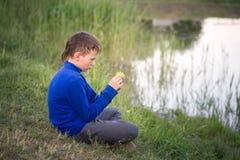 El adolescente se sienta en la orilla del lago Imagenes de archivo