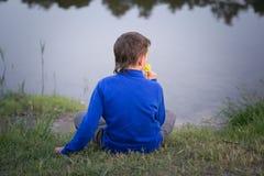El adolescente se sienta en la orilla del lago Foto de archivo