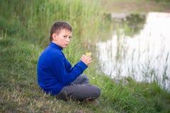 El adolescente se sienta en la orilla del lago Foto de archivo libre de regalías