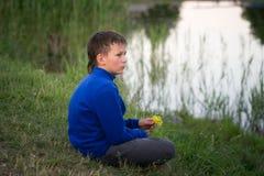 El adolescente se sienta en la orilla del lago Imagen de archivo libre de regalías