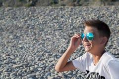El adolescente se sienta en la playa en vidrios azules del sol, Imagen de archivo