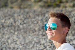 El adolescente se sienta en la playa en vidrios azules del sol, Imagenes de archivo